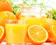 Glass and jug of orange juice and fruits